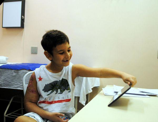 Rede pública de saúde: Mateus se diverte ao brincar com o tablet; ele passou por um procedimento raro e complexo através do SOS Reimplante (Foto: Luiz Barros/Divulgação SES)