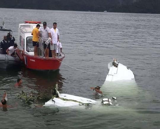Bombeiros tentam retirar corpos que estão presos nas ferragens do avião, no mar de Paraty (foto: Enviada pelo WhatsApp)