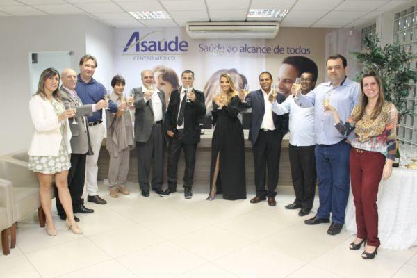 Os empresários Clodoaldo Moren e Silvania Moren fazendo brinde sendo acompanhados pelos profissionais médicos e amigos