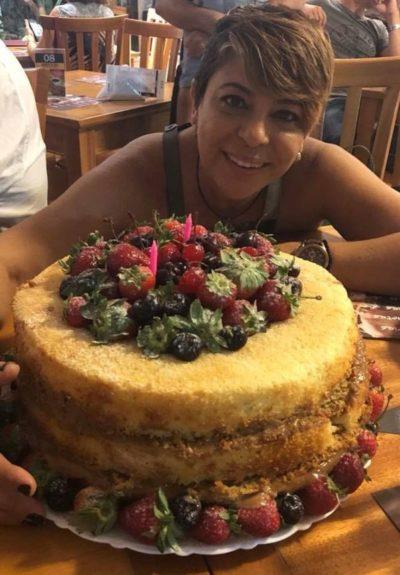 A aniversariante, Cátia Andréia Vianna, na hora do tradicional  'Parabéns pra você' diante de seu belo e delicioso bolo